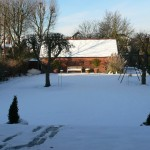 View of barn outhouse from the dining terrace outside the house in the snow